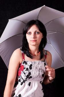 Портрет красивой брюнетки в летнем платье с зонтиком