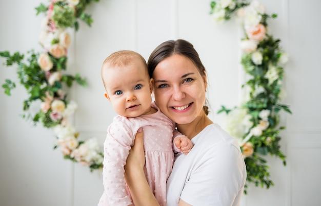 Портрет красивой мамы-брюнетки с маленькой дочкой в розовом платье на белой стене с цветами