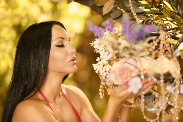 아름다운 갈색 머리의 초상화는 꽃을 킁킁