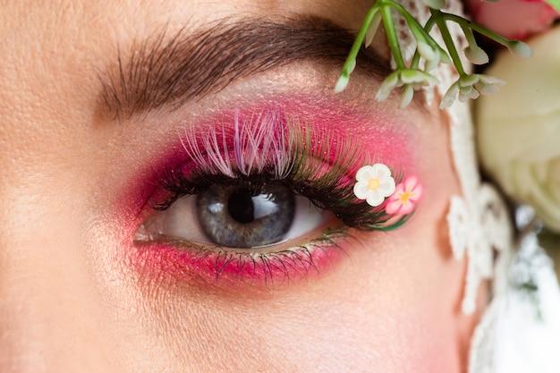 Портрет красивой брюнетки с огромными прямыми ресницами в образе весны с венком из роз на голове на белом.