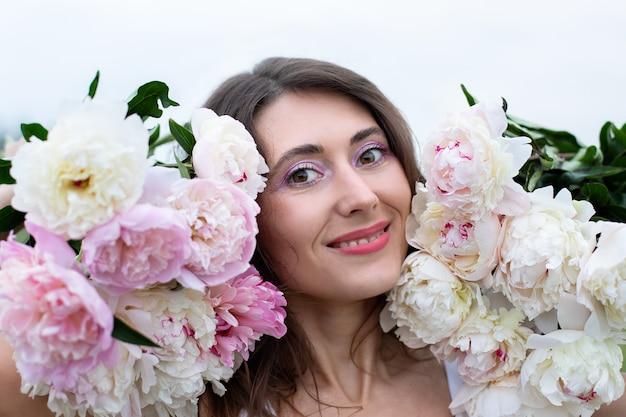 Портрет красивой брюнетки среди пионовидных цветов улыбается женщина с букетом пионов