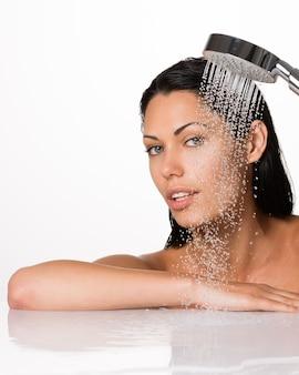 Портрет красивой брюнетки женщины держит в руках душ с падающей водой