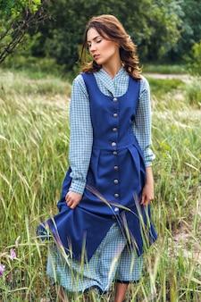 Портрет красивой брюнетки в синем платье в поле