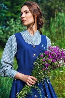 Портрет красивой брюнетки в синем платье в поле Premium Фотографии