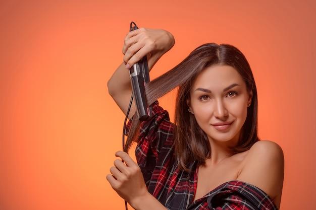 ストレートヘアアイロンで美しいブルネットの女性の肖像画
