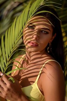彼女の顔にヤシの葉の影を持つ美しいブルネットの女性の肖像画
