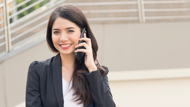 Портрет женщины красивых деловых людей, одетых строго в костюмах, используют смартфон.