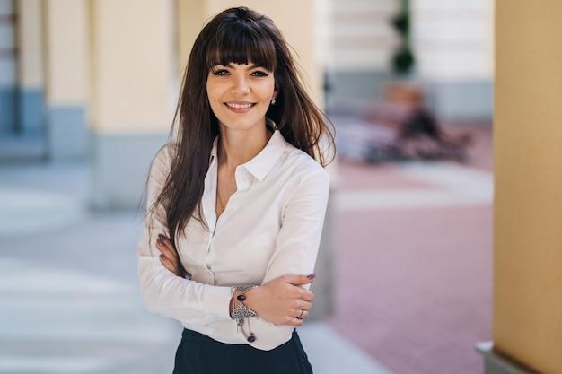 白いシャツと黒のスカートに身を包んだモダンな雰囲気の屋外で美しい女性実業家の肖像画。彼女の仕事をした後幸せな笑顔。