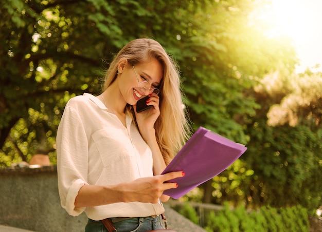 ドキュメントのフォルダーを保持し、屋外を歩きながら電話で話しているカジュアルなスタイルの服を着た美しい実業家の肖像画