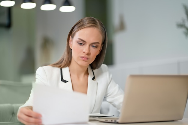 Портрет красивой деловой женщины в белой куртке, работающей с документами в руках, сидя перед ноутбуком.