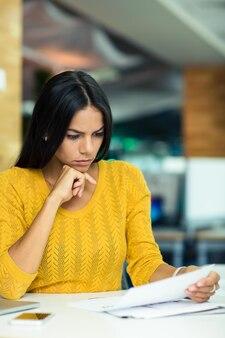 Портрет красивой деловой женщины, читающей документы в офисе