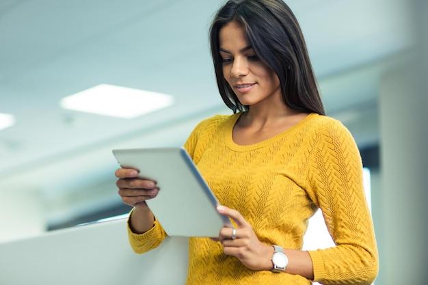 Портрет красивой деловой женщины, использующей планшетный компьютер в офисе