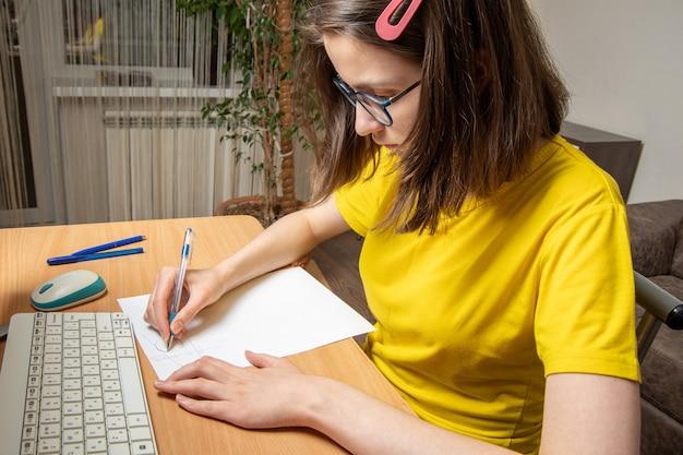 Портрет красивой кавказской девушки в желтой футболке, пишет схему, работа на дому, дистанционное обучение.