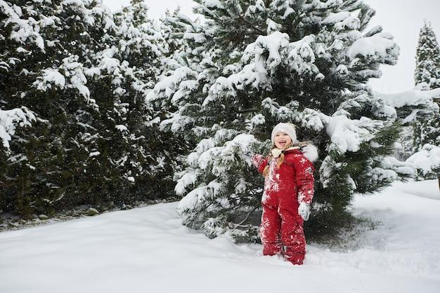 雪に覆われたクリスマスツリーを背景に美しい白人の女の子の肖像画。暖かい冬の服の広告