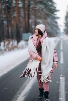 雪に覆われた森の中の道で美しい白人女性の肖像画