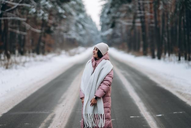눈 덮인 숲을 통해 도로에 아름다운 백인 여자의 초상화