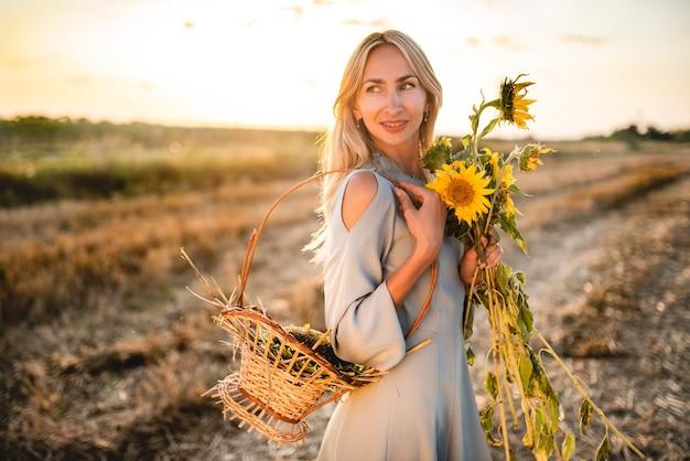 かごとひまわりを腕に抱えて歩く美しい魅力的な女性の肖像画