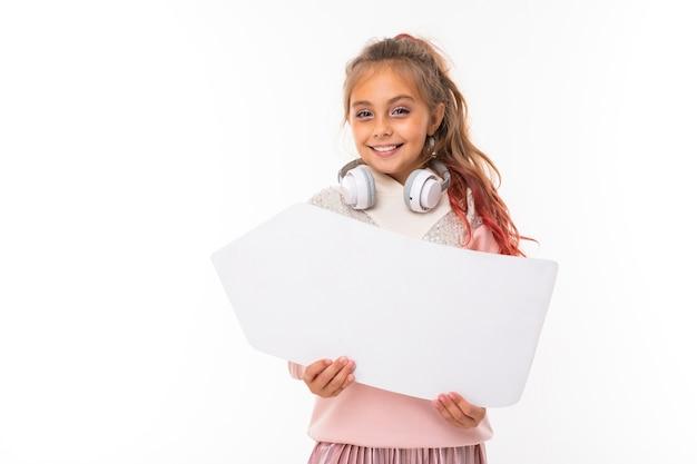 Портрет красивой очаровательной молодой милой девушки в непринужденной зимней одежде с белыми наушниками на белом фоне.