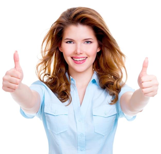 白い背景の上に親指を立ててサインアップの美しい陽気な幸せな女性の肖像画。