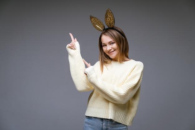 스웨터와 토끼 귀에 아름 다운 쾌활 한 젊은 여자의 초상화는 회색 장면에 측면에 그녀의 손가락을 보여줍니다