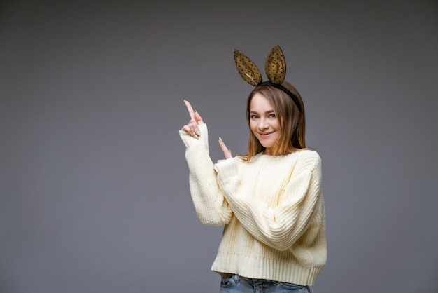 스웨터와 토끼 귀에 아름 다운 쾌활 한 젊은 여자의 초상화는 회색 벽에 측면에 그녀의 손가락을 보여줍니다