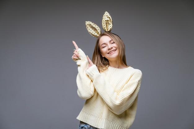 스웨터와 토끼 귀에 아름 다운 쾌활 한 젊은 여자의 초상화는 회색 측면에 그녀의 손가락을 보여줍니다