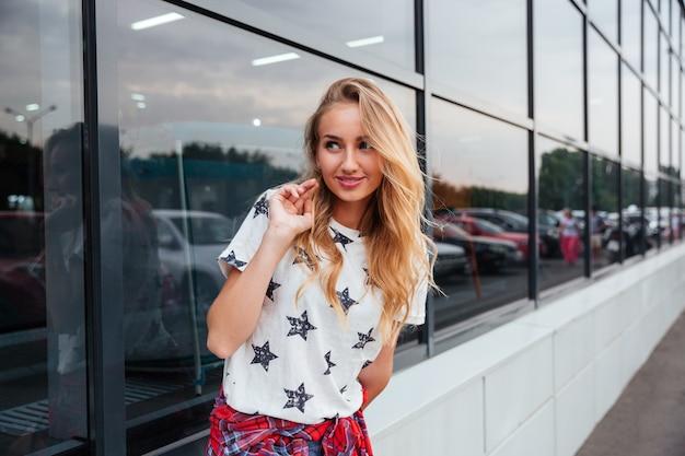 ガラスの建物で屋外に立っている美しい陽気な若い女性の肖像画