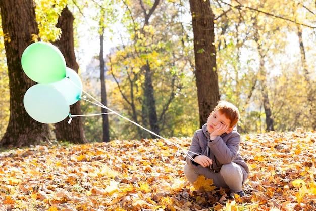 Портрет красивого ребенка-мальчика во время прогулки в парке с воздушными шарами
