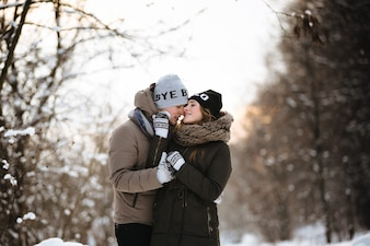 Portrait of a beautiful couple dressed in winter clothes in the winter cold day.