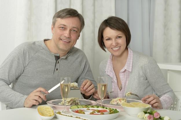 美しいカップルの肖像画は、レストランで夕食をとります