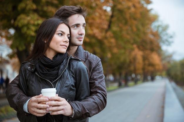 屋外を離れて見ているコーヒーと美しいカップルの肖像画