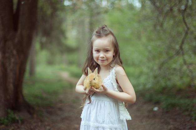 Портрет красивой милой девушки в лесу. в руках девочка держит красного кролика.