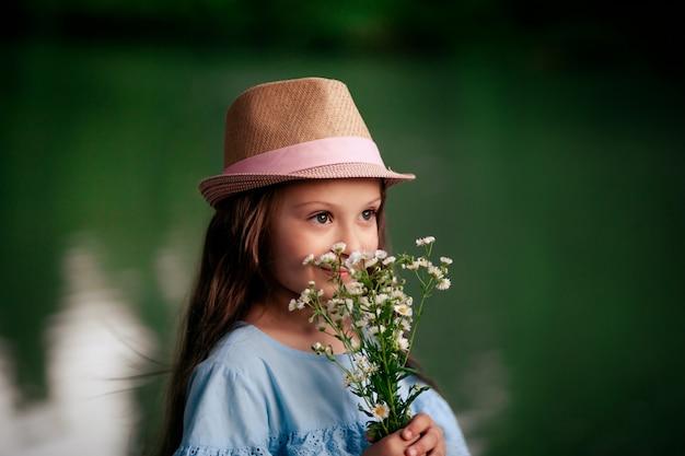 Портрет красивой милой девочки 7-8 лет на природе, и ребенок держит цветы в руках, у стены реки.