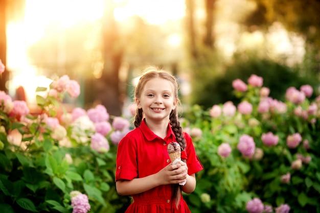Портрет красивая милая девушка 7-8 лет с мороженым в руках, ребенок в парке развлечений в летнее время.