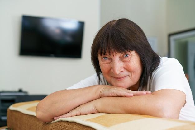 退職を楽しんでいる自宅のソファに座って笑っている美しい年配の女性の肖像画