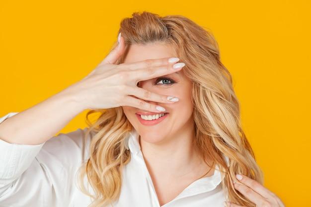 巻き毛のブロンドの髪を持つ美しい熱狂的な女性の肖像画は彼女の目を閉じ、彼女の指を通して見える笑顔