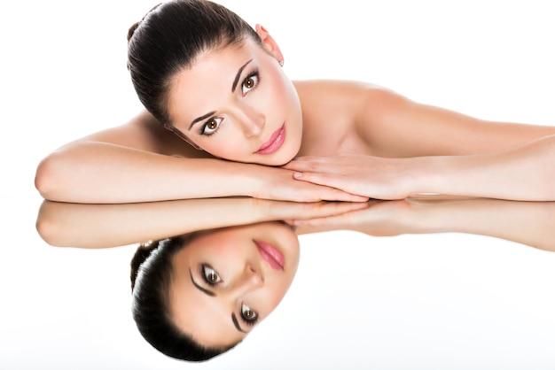 鏡で健康な肌の反射を持つ若いきれいな女性の美しい顔の肖像画