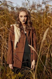 Портрет красивой модницы в зарослях осенней травы