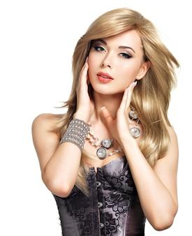 明るいメイクで美しいファッション女性の肖像画。シルバーのアクセサリーでポーズをとるグラマーガールのかなりセクシーな顔。