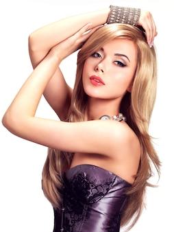 Портрет красивой модной женщины с ярким макияжем. довольно сексуальное лицо гламурной девушки, позирующей с серебряным аксессуаром.