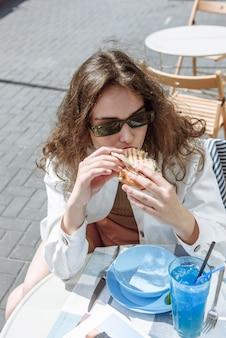앉아있는 동안 테이블에서 식사하는 레스토랑에서 아름 다운 유행 갈색 머리 여자의 초상화