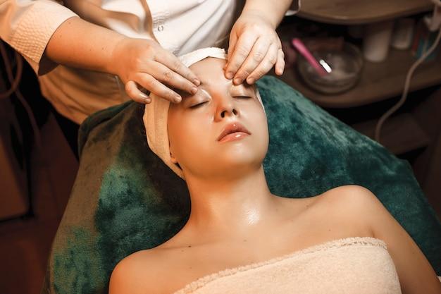 Портрет красивой женщины, опирающейся на спа-кровать с закрытыми глазами, делающей массаж лица с гиалуроновой кислотой.