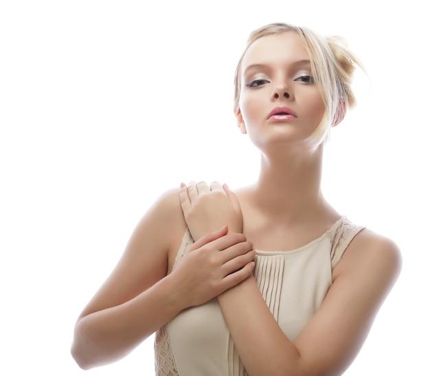 Портрет красивой женской модели в белом платье на белом фоне