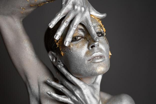 スタジオで肌と髪に金と銀のペイントを施した美しい女性モデルのポートレート。