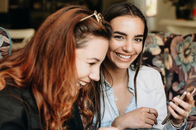 Портрет красивой девушки с темными волосами, смотрящей в камеру, смеясь, держа смартфон, в то время как ее подруга отводит взгляд от смеха.