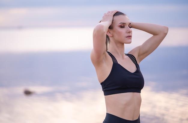 Портрет красивой фитнес-модели на фоне моря на закате