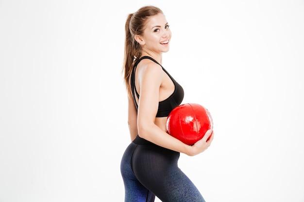 빨간 공을 들고 있는 아름다운 피트니스 여성의 초상화