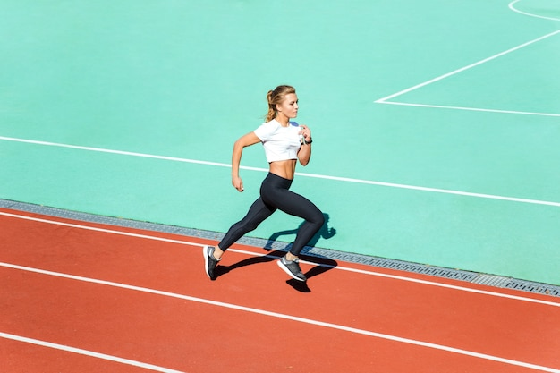 スタジアムで走っている美しいフィットネス女性の肖像画
