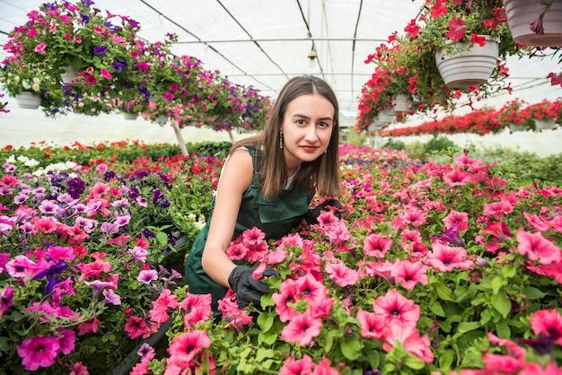 花のある温室でポーズをとる美しい花屋の女性の肖像画。春