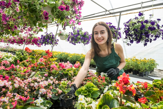 꽃과 온실에서 포즈를 취하는 아름다운 꽃집 여자의 초상화
